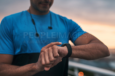 Buy stock photo Cropped shot of a man checking the time during a workout in the city