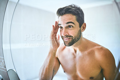 Buy stock photo Cropped shot of a handsome young man looking in the mirror and examining his face inside his bathroom at home