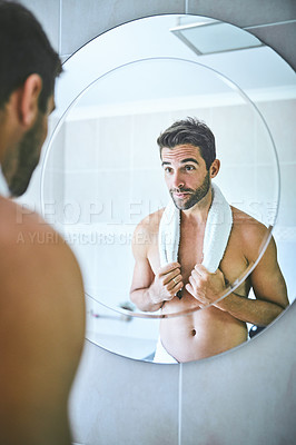 Buy stock photo Cropped shot of a handsome young man looking at his face in the mirror inside his bathroom at home