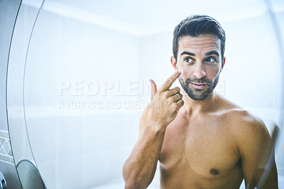 Buy stock photo Cropped shot of a handsome young man applying moisturizer to his face in the bathroom at home