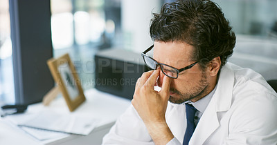 Buy stock photo Shot of a young doctor looking stressed out while working at his desk