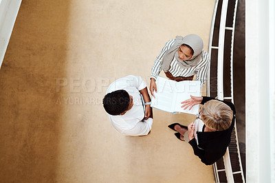 Buy stock photo High angle shot of a group of businesspeople having a discussion while going through paperwork together in an office
