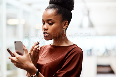 Buy stock photo Shot of a young businesswoman applying lipstick while using her cellphone as a mirror in an office