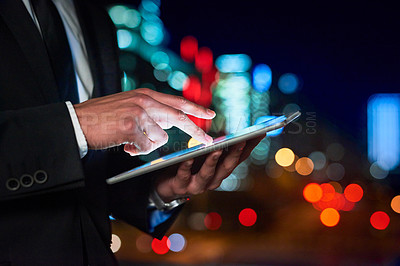 Buy stock photo Cropped shot of an unrecognizable businessman using his digital tablet outdoors in the city at night