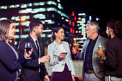 Buy stock photo Cropped shot of a group of businesspeople having drinks and celebrating on a rooftop in the city at night