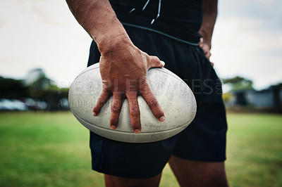 Buy stock photo Cropped shot of an unrecognizable rugby player holding a rugby ball on the field during the day