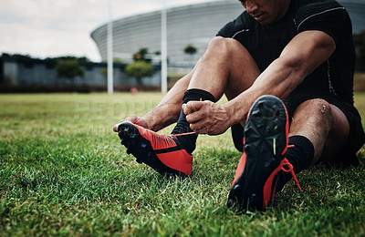 Buy stock photo Cropped shot of an unrecognizable rugby player tying his shoelaces while sitting on the field during the day