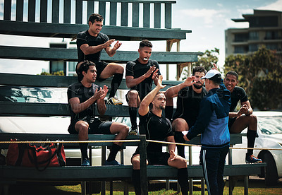 Buy stock photo Cropped shot of a team of rugby players clapping for their coach while sitting on the bench near the field