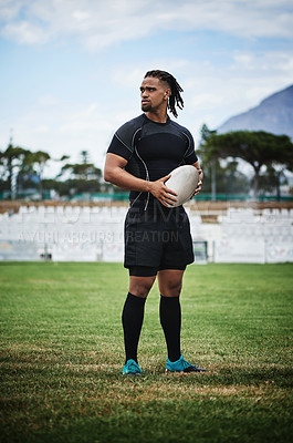 Buy stock photo Full length shot of a handsome young rugby player holding a rugby ball while standing on the field
