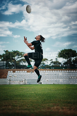 Buy stock photo Full length shot of a handsome young rugby player catching a ball mid-air on the field