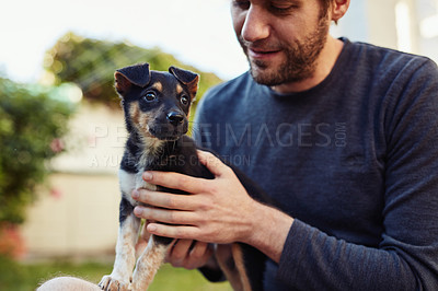 Buy stock photo Shot of a happy young man spending time with his adorable little puppy outside