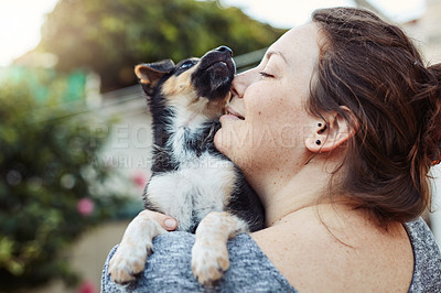 Buy stock photo Shot of a happy young woman kissing and spending time with her adorable little puppy outdoors