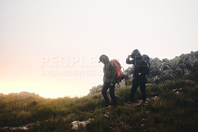 Buy stock photo Shot of two friends out hiking in the mountains on a foggy day