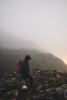 Buy stock photo Shot of a man wearing his backpack while out for a hike in the mountains with his dog