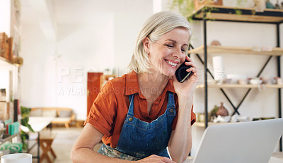 Buy stock photo Shot of a mature woman using a laptop and smartphone while working in a pottery studio