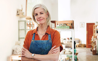 Buy stock photo Shot of a confident mature woman working in a pottery studio