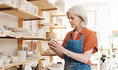 Buy stock photo Shot of a mature woman working in a pottery studio