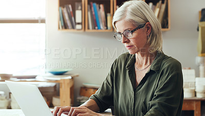 Buy stock photo Shot of a mature woman using a laptop while working in a pottery studio