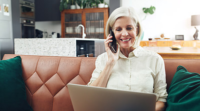 Buy stock photo Cropped shot of an attractive mature woman sitting alone and using her laptop while talking on her cellphone at home