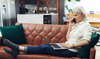 Buy stock photo Full length shot of an attractive mature woman sitting and using her laptop while talking on her cellphone at home