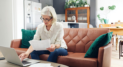 Buy stock photo Cropped shot of an attractive mature woman sitting alone and using a laptop to go through her finances at home