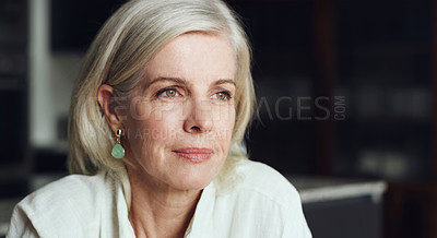 Buy stock photo Cropped shot of an attractive mature woman sitting alone and looking contemplative during a day at home