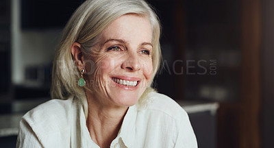 Buy stock photo Cropped shot of an attractive mature woman sitting alone and enjoying a relaxing day at home