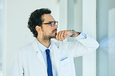 Buy stock photo Shot of a young doctor looking out the window in a hospital