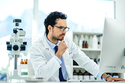Buy stock photo Shot of a young scientist looking thoughtful while working on a computer in a lab