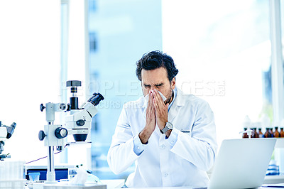 Buy stock photo Shot of a young scientist blowing his nose while working in a lab