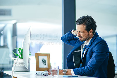 Buy stock photo Shot of a young businessman experiencing neck pain while working at his desk