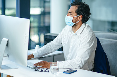 Buy stock photo Shot of a young businessman using a computer and mask at his work desk