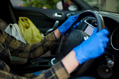 Buy stock photo Cropped shot of an unrecognizable woman driving a car with gloves on during the day