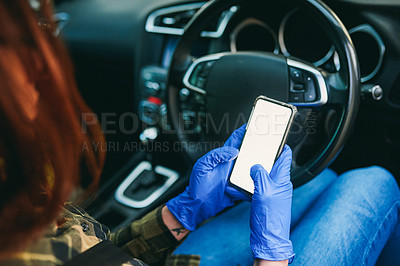 Buy stock photo Cropped shot of an unrecognizable woman using a smartphone while wearing gloves in her car