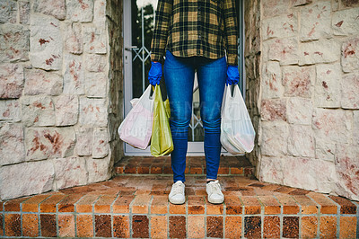 Buy stock photo Cropped shot of an unrecognizable woman holding plastic bags full of groceries at her front entrance at home