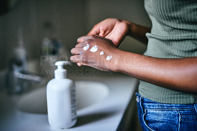 Buy stock photo Cropped shot of an unrecognizable woman sanitizing her hands at home