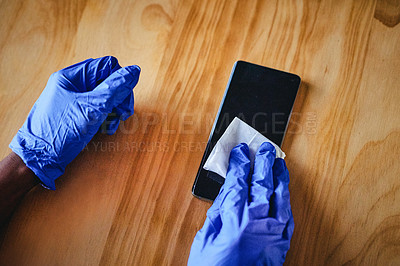 Buy stock photo High angle shot of an unrecognizable woman cleaning the screen of her smartphone at home
