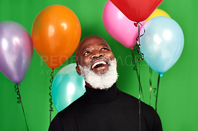 Buy stock photo Studio shot of a man posing against a green background with balloons around him