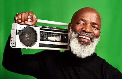 Buy stock photo Studio shot of a senior man holding up a vintage radio against a green background