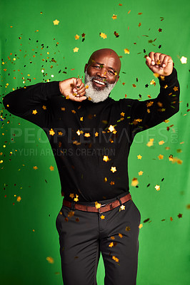 Buy stock photo Shot of a senior man dancing while confetti falls over him against a green background