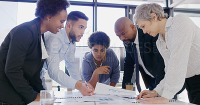 Buy stock photo Cropped shot of a diverse group of businesspeople standing together and brainstorming during a meeting in the office