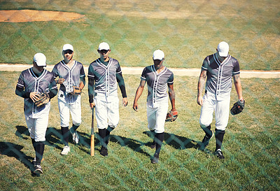 Buy stock photo Shot of a group of young men walking onto a baseball field