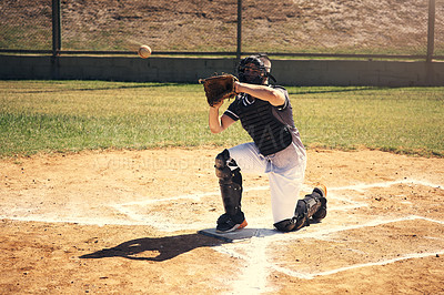 Buy stock photo Shot of a young man catching a ball during a baseball match