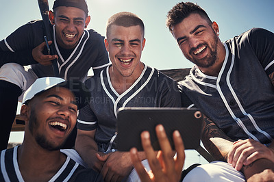 Buy stock photo Shot of a group of young men using a smartphone after playing a baseball game
