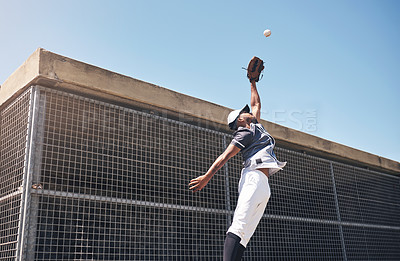 Buy stock photo Shot of a young man catching a ball at a baseball match