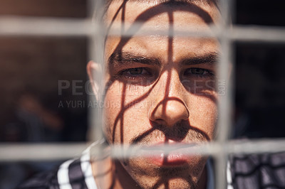 Buy stock photo Shot of a young man watching a game of baseball from behind the fence