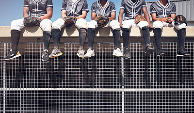 Buy stock photo Cropped shot of a group of men sitting on top of the dugout and watching a baseball game