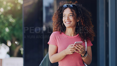 Buy stock photo Cropped shot of a young woman using her cellphone while walking through the city