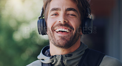 Buy stock photo Cropped shot of a young man wearing headphone while walking through the city