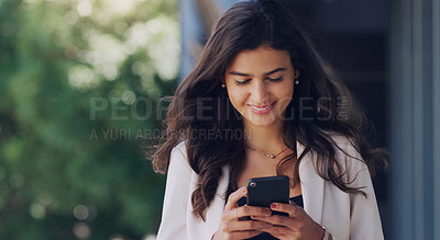 Buy stock photo Shot of a beautiful young woman using her cellphone while standing outdoors